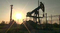 An oil pump jack in action at sunset – backlight Stock Footage
