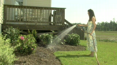 Young Woman Waters Shrubs Stock Footage