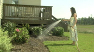 Stock Video Footage of Young Woman Waters Shrubs