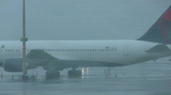 Rainy runway with plane on tarmac Stock Footage