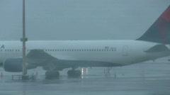 rainy runway with plane on tarmac - stock footage