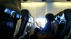 Woman reading a book whilst on a airplane flight 1 Stock Footage