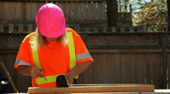 Woman in pink hardhat takes call Stock Footage
