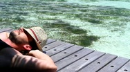 Stock Video Footage of Handsome man resting near water at Maldives