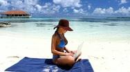 Beautiful woman working on laptop near water at Maldives Stock Footage