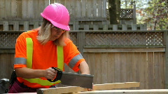 Woman in pink hardhat uses hand saw - stock footage