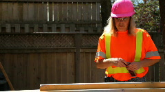 Woman in pink hardhat levels wood Stock Footage