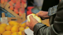 Man cutting a lemon at the market Stock Footage