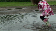 Puddle Jumping - Little girl frog hops - stock footage