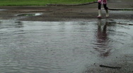 Puddle Jumping - Little girl runs thru large puddle Stock Footage