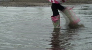 Puddle Jumping - Little girl splashes then runs off Stock Footage