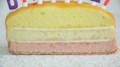 PAN, CU, burning birthday candles on cake Stock Footage