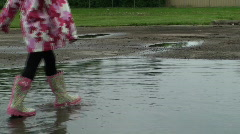 Puddle Jumping - Little girl spinning Stock Footage