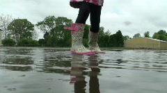 Puddle Jumping - Little girl's rainboots up close Stock Footage