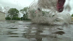 Puddle Jumping - Mother and daughter splash each other close up Stock Footage