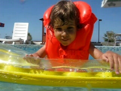 Girl on inflatable mattress in water pool Stock Footage