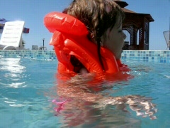 Girl in life jacket swims in outdoor water pool Stock Footage