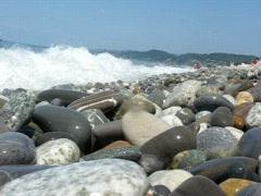 Sea surf covers camera lying on beach Stock Footage