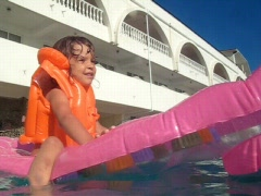 Girl on inflatable mattress in swimming pool Stock Footage