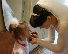 Bride in wedding gown puts on lipstick her daughter Stock Footage
