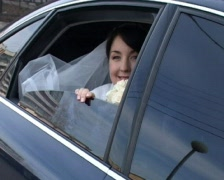 Bride in wedding gown sits in car and waves her hand Stock Footage