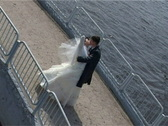Kissing groom and bride stands on bridge Stock Footage