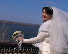 Bride with bouquet stands against river Stock Footage