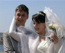 Bride and groom stands against river Stock Footage