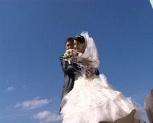 bridegroom hugs bride stands against sky - stock footage
