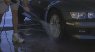 At the manual car wash - 3 - power spray the tires and wheels Stock Footage