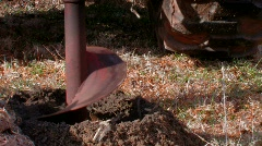 Drilling post hole with backhoe and auger  Stock Footage