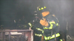 Firefighters leaving smoking building Stock Footage