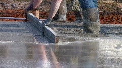Worker leveling freshly poured concrete  Stock Footage