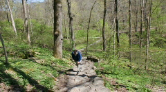 Elderly man walking up a step path in the woods Stock Footage