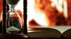 hourglass and an open book. - stock footage