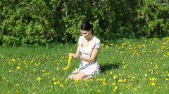 she weaves a wreath of dandelions - stock footage