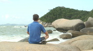 Man meditating on a rock Stock Footage
