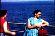 2 women on a ship wind blows up dress 1950's Stock Footage