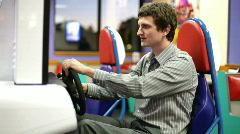 Businessman playing Arcade Racing Game Stock Footage