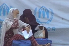 Women in Burqa sit outside UNHCR Camp in Pakistan Stock Footage