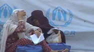 Stock Video Footage of Women in Burqa sit outside UNHCR Camp in Pakistan