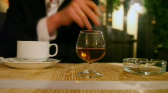 Lunch place with cup of coffee, glass, ashtray and smoking person Stock Footage