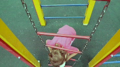 Girl climb up on chain ladder Stock Footage