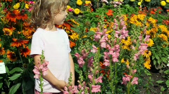 Girl goes among set of flowers in garden examines Stock Footage