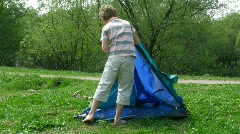 The boy establishes tent on a glade Stock Footage