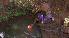 Ethiopia:Girl Collects Water from a Dirty Water Hole  - stock footage