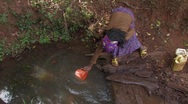 Stock Video Footage of Ethiopia:Girl Collects Water from a Dirty Water Hole