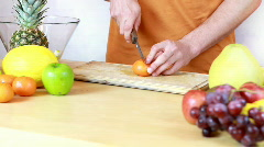Slicing mandarine - Preparing fruit salad Stock Footage