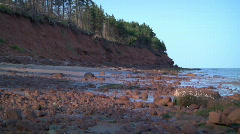Red sand cliff and stony beach Stock Footage