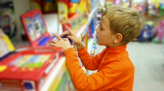 Boy pushes buttons of electonic toy in shop Stock Footage